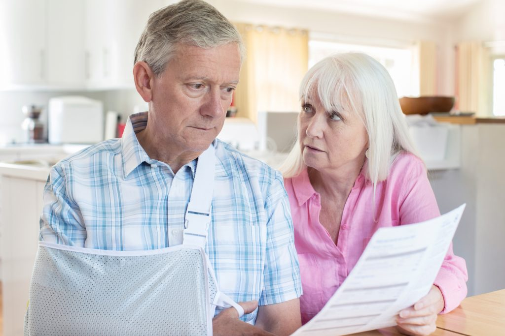 husband and wife looking over medical injury bill after ICBC adjusted