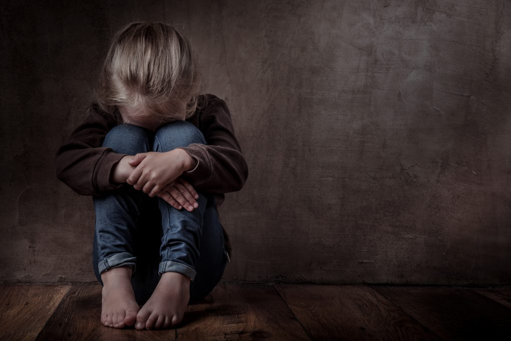 sad little girl sitting against the wall crying