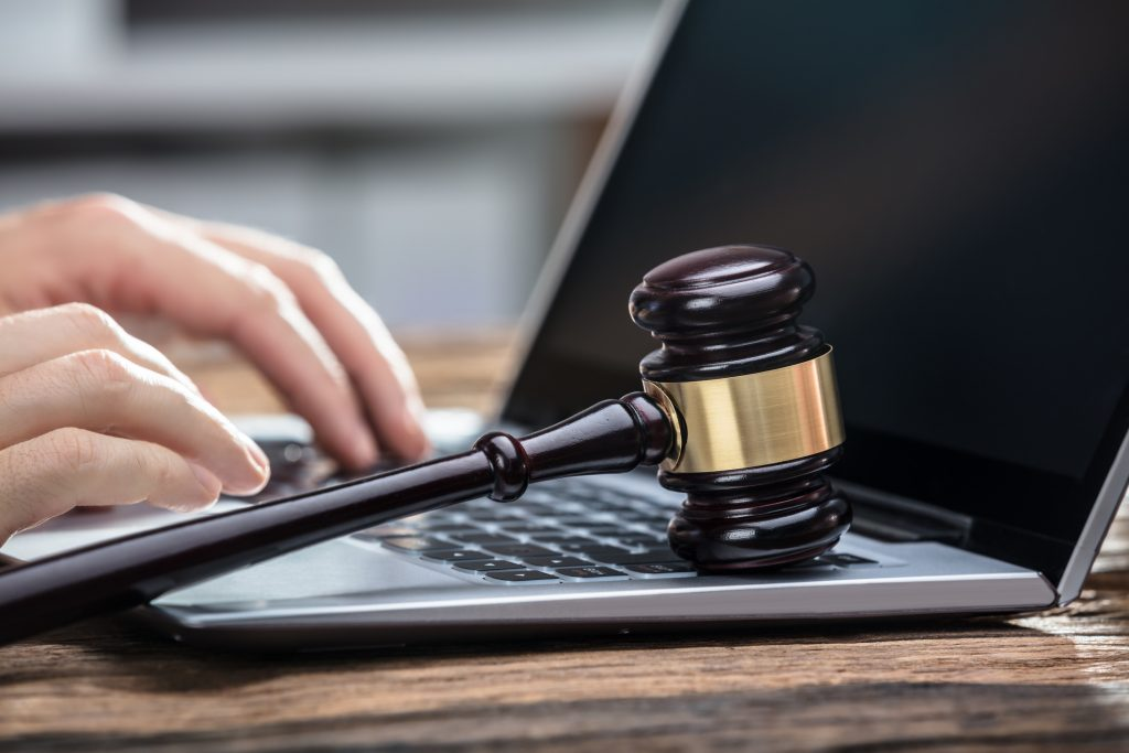A gavel and computer emphasizing the search for legal council