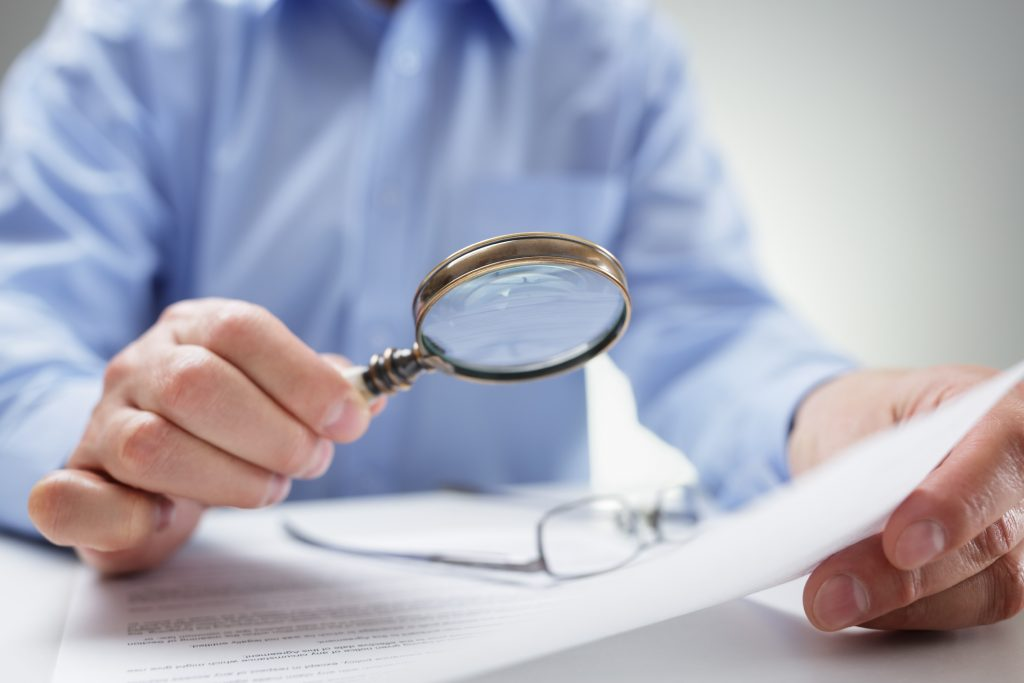 A magnifying glass reading fine print in contracts