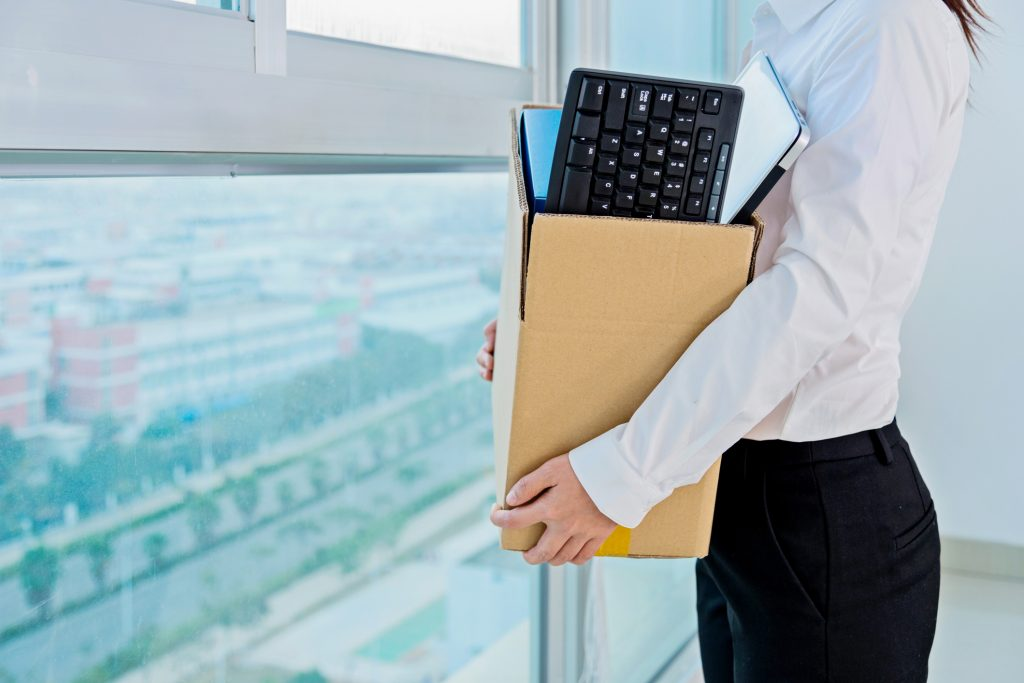 A woman holding a box in an office after seeking employment claims and aggravated damages