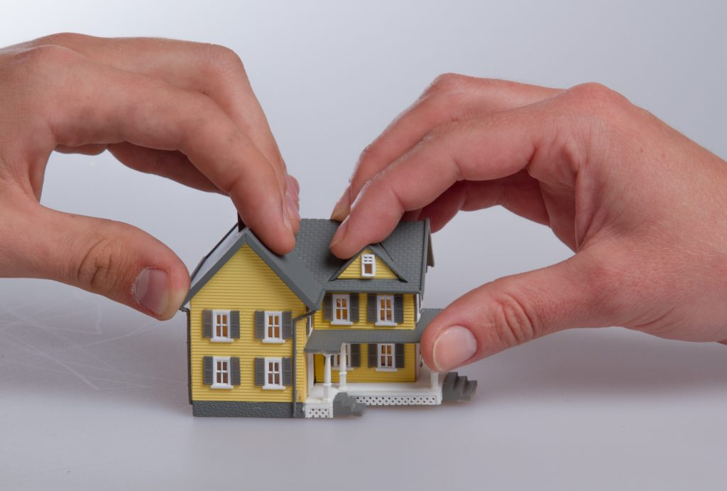 Human Hands Holding a Model of a House as they separate over divorce