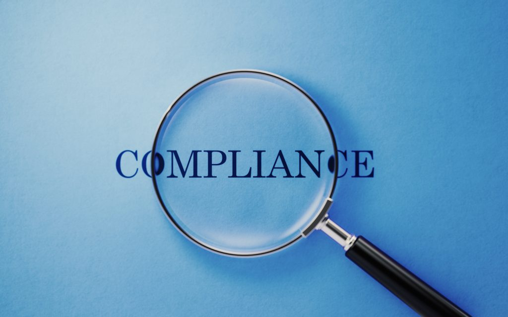 Magnifying glass emphasizing compliance with CBCA Regulations